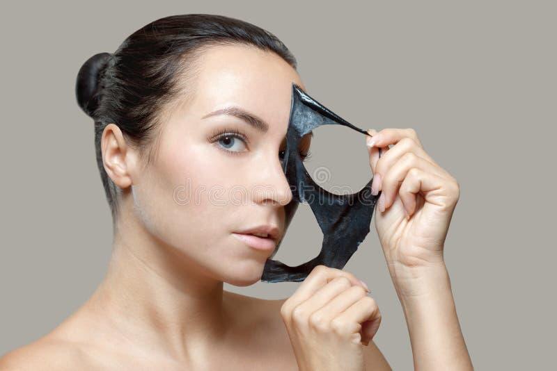 Een zwart masker aan het gezicht van een mooie vrouw stock fotografie