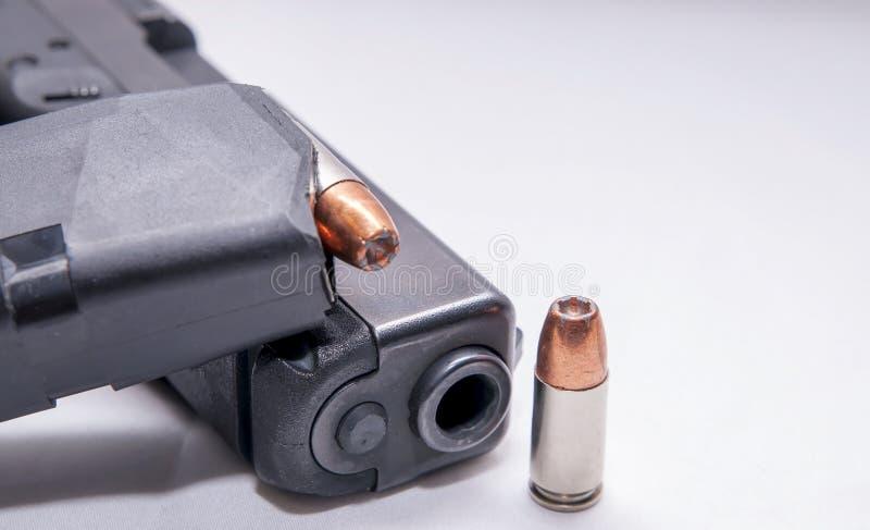 Een zwart 9mm pistool met een geladen tijdschrift bovenop het en één enkele 9mm holle puntkogel naast het stock afbeeldingen