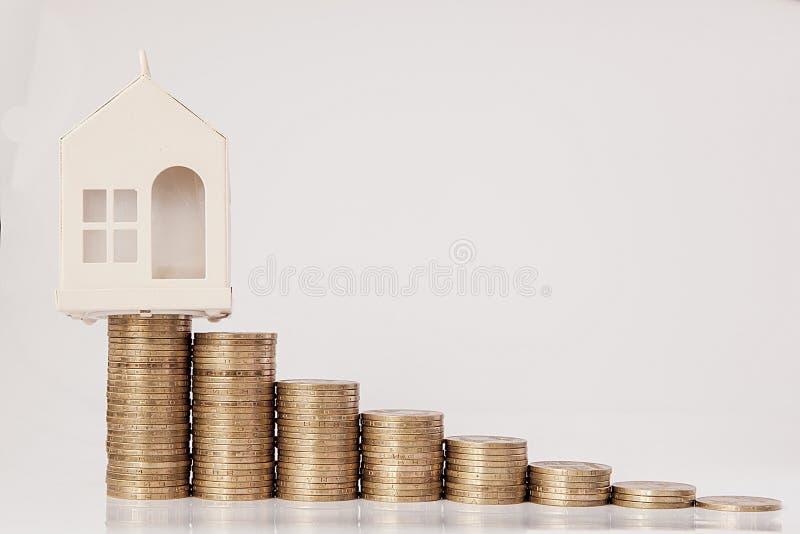 Een zwart model van een auto en een huis met muntstukken in de vorm van een histogram op een witte achtergrond Concept het lenen, stock afbeeldingen