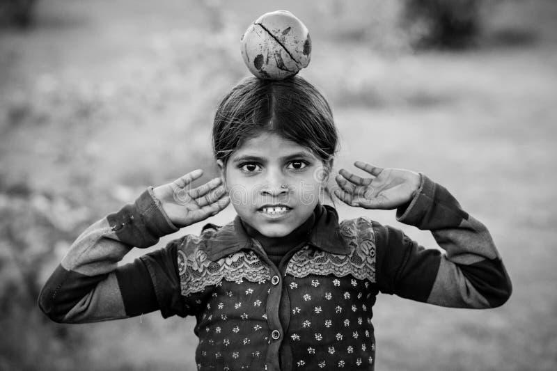 Een zwart-wit beeld met een Indisch meisje met een fruit op haar hoofd royalty-vrije stock foto's