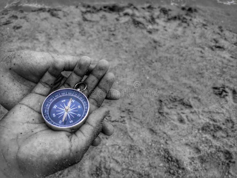 Een zwart-witte fotografie met holding op een kompas die uw richting en uw navigatie tonen door onder ogen te zien aan de oceaan royalty-vrije stock afbeelding