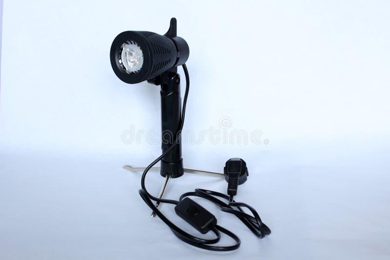 Een zwarte fotograaf` s lamp op driepoot voor lichte doos stock fotografie