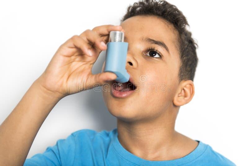 Een zwarte Jongen die een astmainhaleertoestel met behulp van royalty-vrije stock afbeeldingen