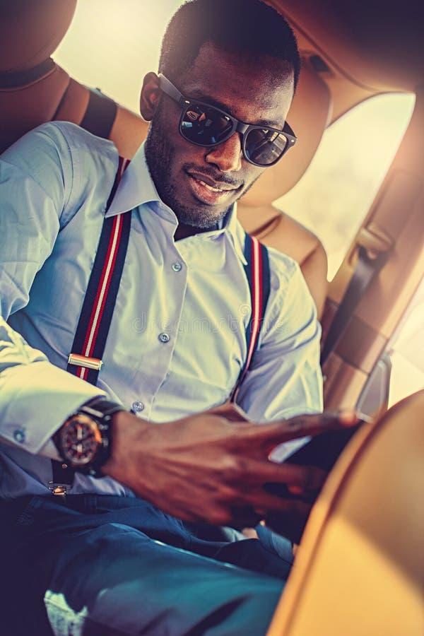 Een zwarte mens die in zonnebril in de auto zitten stock afbeelding