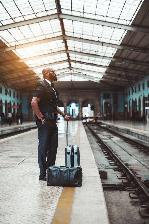 Een zwarte mens wacht op een trein royalty-vrije stock afbeeldingen