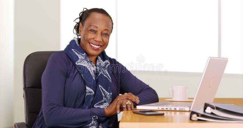 Een zwarte onderneemster stelt voor een portret bij haar bureau stock foto