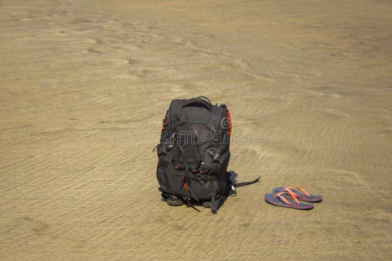 Een zwarte rugzak en purpere wipschakelaars op het zand royalty-vrije stock fotografie