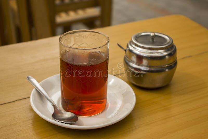 Een zwarte thee in een glaskop op een schotel met een lepel op een houten lijst met een kom van de metaalsuiker royalty-vrije stock fotografie