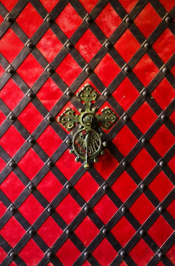 Een zwarte vervalsing op de rode ijzeren deur Oude wijndeur met ijzerhandvat stock afbeeldingen