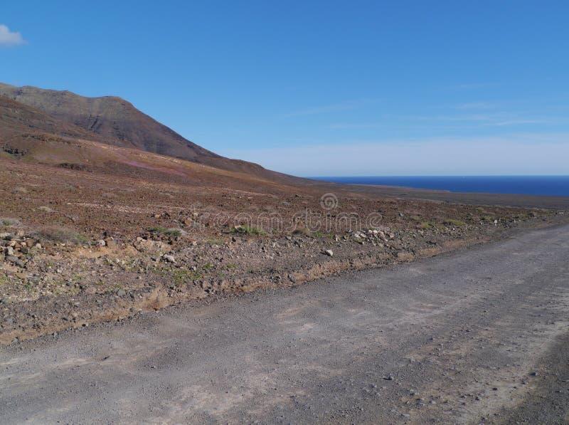 Een zwarte weg in de kleurrijke bergen op Fuerteventura stock fotografie