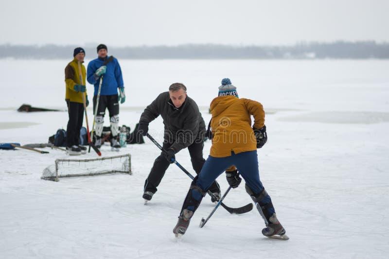 Eenager-Mädchen, das kleines Ziel das reifer verteidigender Mann beim Spielen des Hockeys in Angriff nimmt lizenzfreies stockbild
