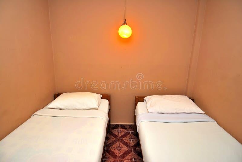 Eenspersoonsbedden in donkere hotelruimte stock fotografie