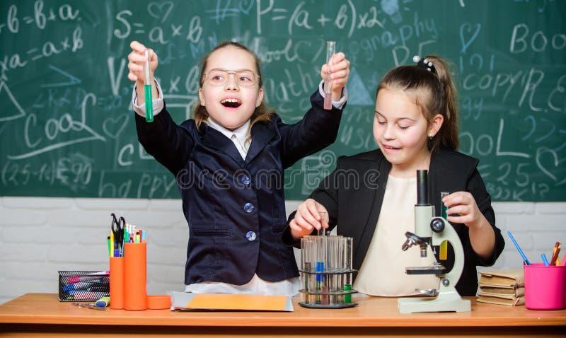 Eenvormige bezig van de meisjesschool met test hun hypothese Retro laboratoriummateriaal en boeken dichtbij verlichtingskaarsen o stock afbeelding