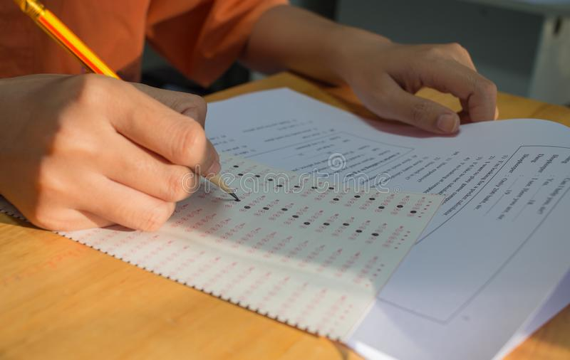 Eenvormige School Aziatische studenten die examens nemen die antwoord optische vorm met potlood in middelbare schoolklaslokaal sc royalty-vrije stock foto