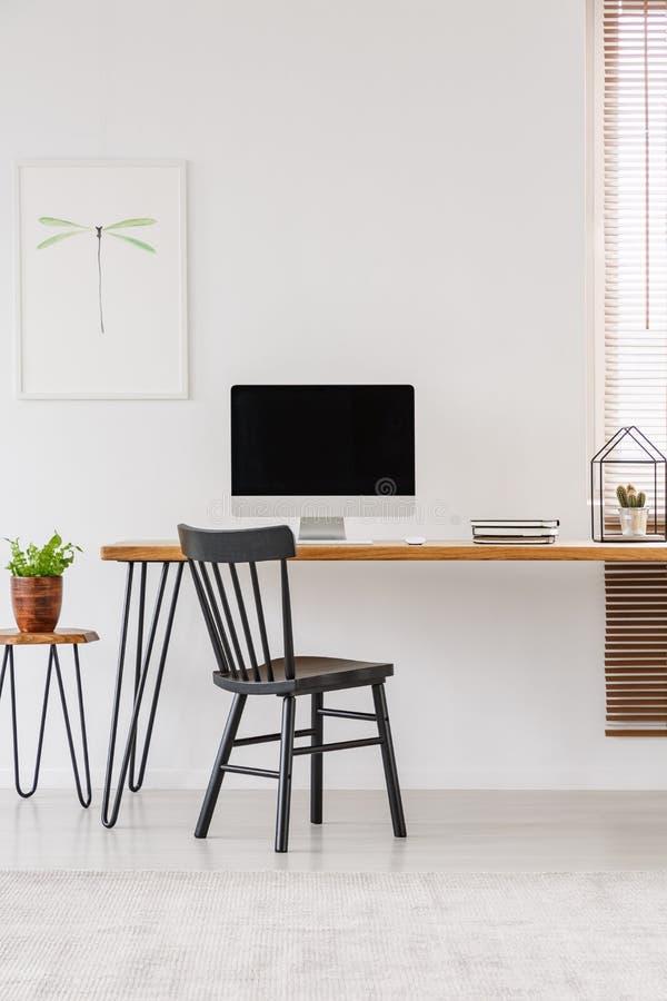 Eenvoudig binnenland van een huisbureau met zwarte stoel die zich bij a bevinden royalty-vrije stock foto's