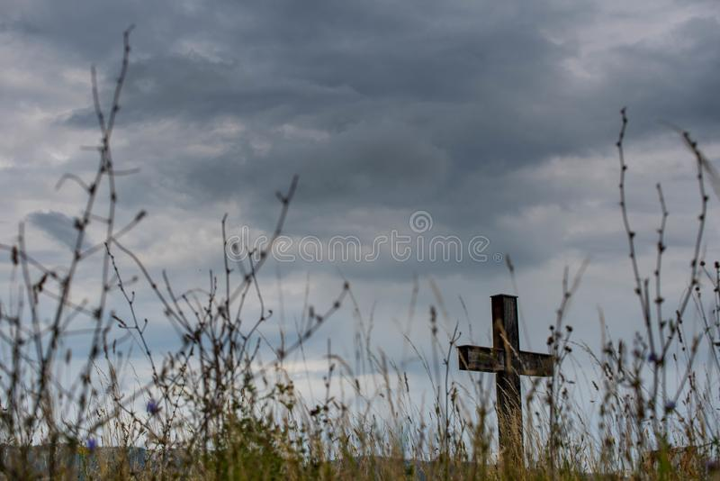 Eenvoudig eiken katholiek kruis, gras in de voorgrond, onweerswolken royalty-vrije stock afbeelding