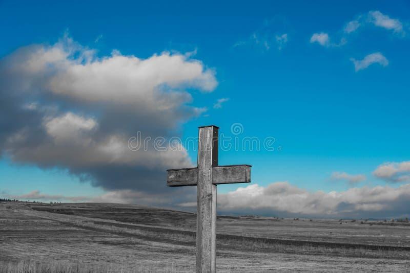 Eenvoudig eiken katholiek kruis in zwart-witte, blauwe hemel met stormclouds stock foto's