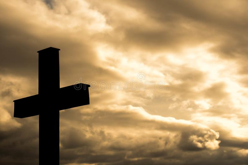 Eenvoudig houten katholiek dwarssilhouet, dramatische oranje onweerswolken op de achtergrond, stock afbeeldingen