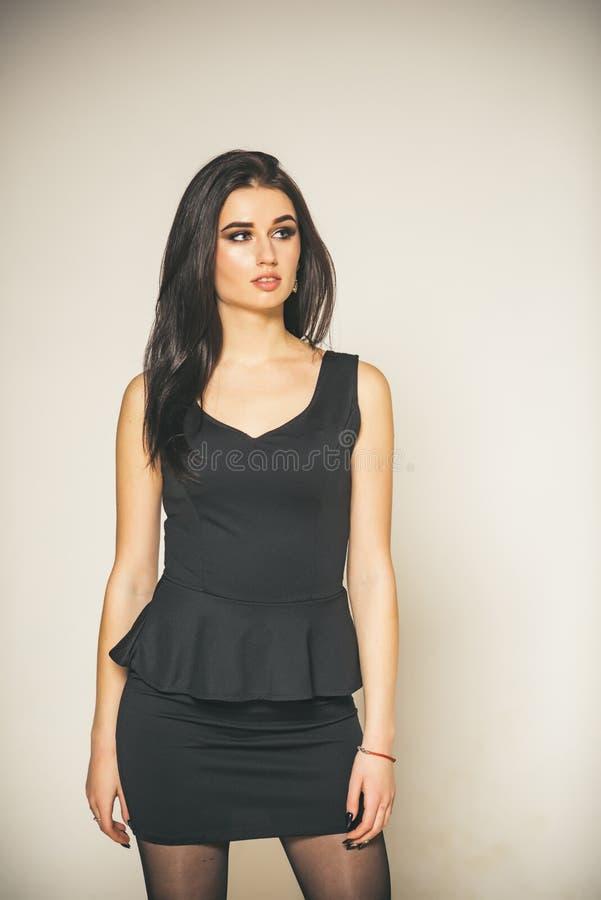 Eenvoudig Overweldigend Damebrunette in klassieke elegante zwarte kleding en make-up Vrouw schitterend in modieuze uitrusting stock fotografie