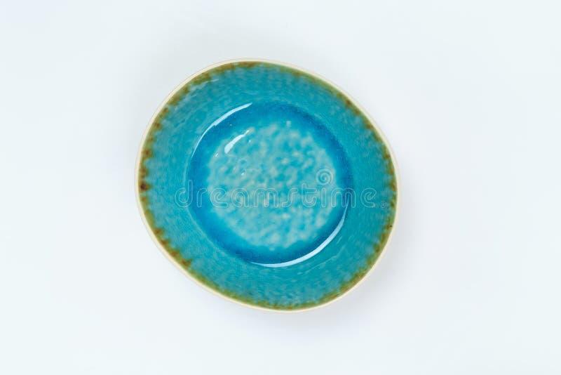 Eenvoudig rustiek met de hand gemaakt blauw aardewerk op een witte achtergrond stock foto