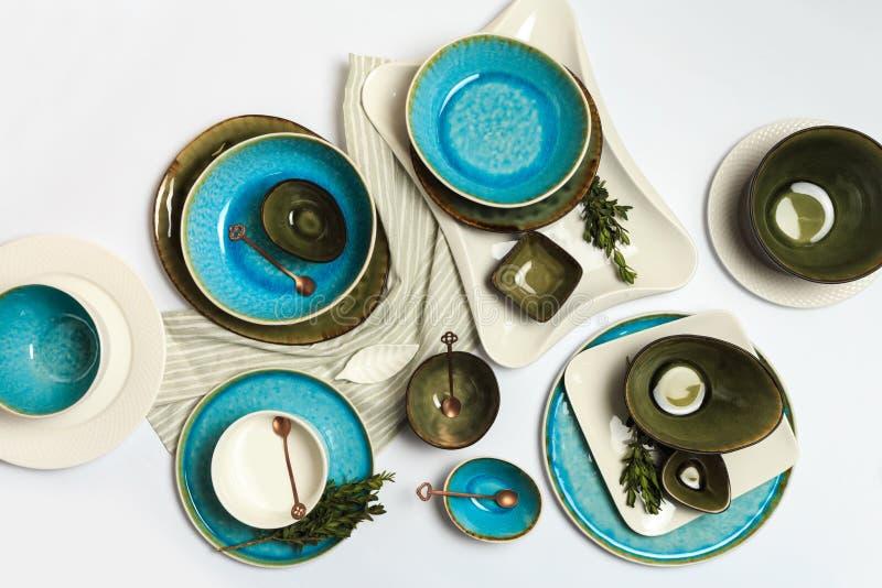 Eenvoudig rustiek met de hand gemaakt blauw en groen aardewerk tegen witte houten muur: schotel, stapel kommen Hoogste mening royalty-vrije stock foto's