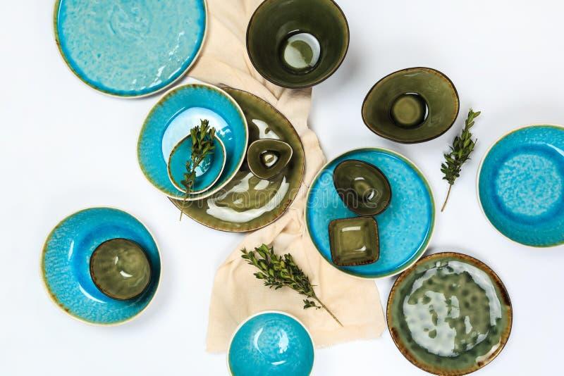 Eenvoudig rustiek met de hand gemaakt blauw en groen aardewerk tegen witte houten muur: schotel, stapel kommen Hoogste mening royalty-vrije stock afbeelding