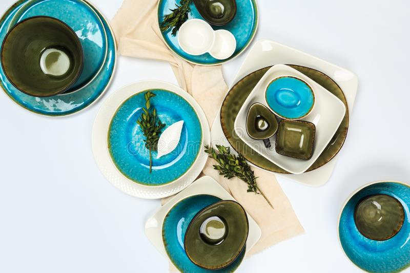 Eenvoudig rustiek met de hand gemaakt blauw en groen aardewerk tegen witte houten muur: schotel, stapel kommen Hoogste mening stock afbeelding