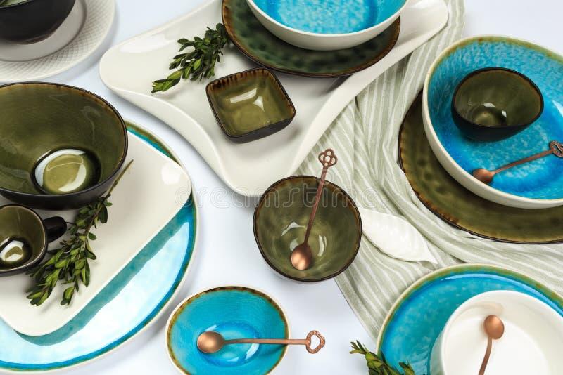 Eenvoudig rustiek met de hand gemaakt blauw en groen aardewerk tegen witte houten muur: schotel, stapel kommen Hoogste mening stock fotografie
