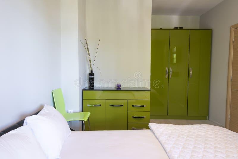 Eenvoudig slaapkamerbinnenland met groot comfortabel bed en groen meubilair Binnenlandse fotografie stock foto's