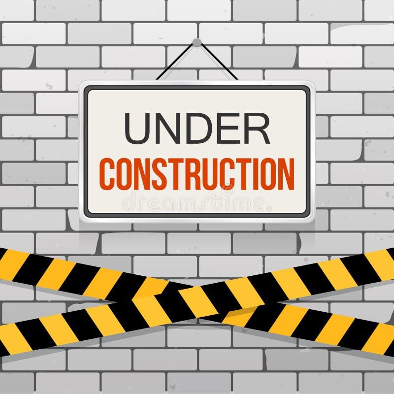 Eenvoudig wit teken met tekst ` in aanbouw ` het hangen op een grijze bakstenen muur met waarschuwingsbanden Het concept van de t stock illustratie