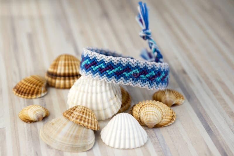 Eenvoudige blauwe met de hand gemaakte eigengemaakte natuurlijke geweven armbanden één van vriendschap op witte houten lijst en o royalty-vrije stock afbeeldingen