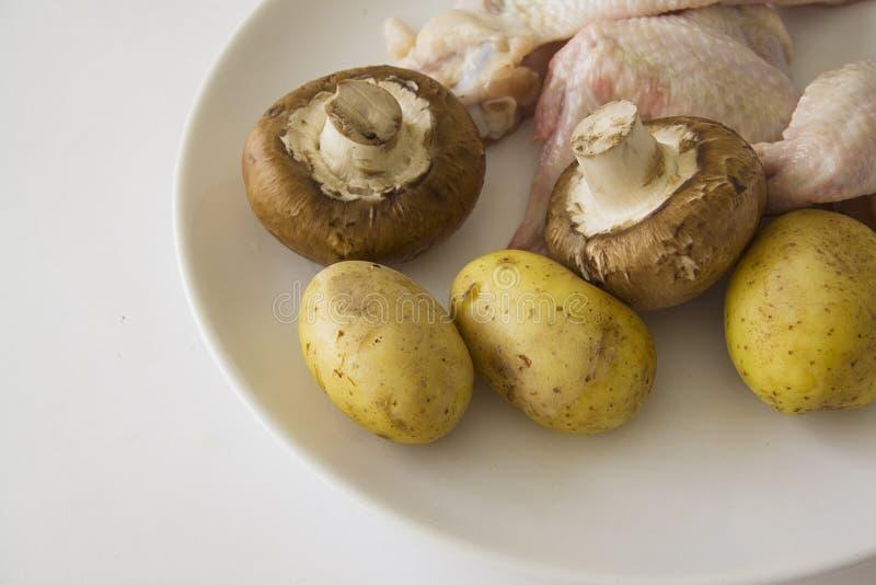 Eenvoudige close-upfoto van Ruwe kippenvleugels met aardappel en champignons royalty-vrije stock afbeelding