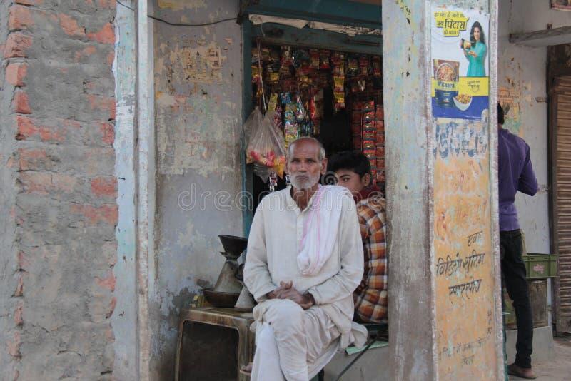 Eenvoudige dorpsbewoner die uit zijhuis in India situeren stock fotografie