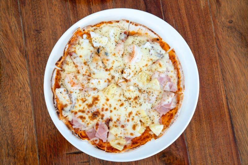 Eenvoudige en basisnormali solated volledige cirkelpizza in Witte schotel op houten lijst met het knippen van wegen stock afbeeldingen