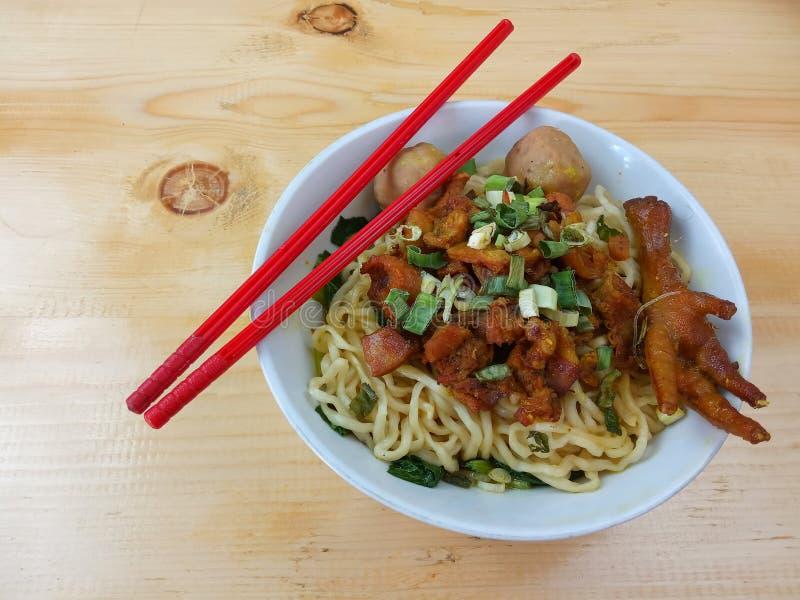 Eenvoudige Foto, Hoogste Weergeven, bakso van Mie Ayam ceker, Kippennoedel bij witte kom en rood plastic eetstokje bij houten lij stock foto's