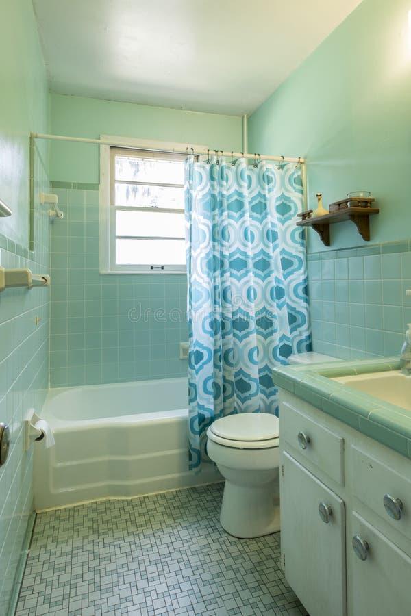 Eenvoudige gedateerde jaren '50badkamers met groene tegel stock foto