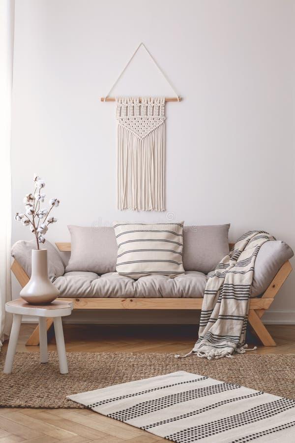Eenvoudige, houten kruk op een rieten deken in een vreedzaam woonkamerbinnenland met een mooie met de hand gemaakte decoratie op  stock afbeeldingen