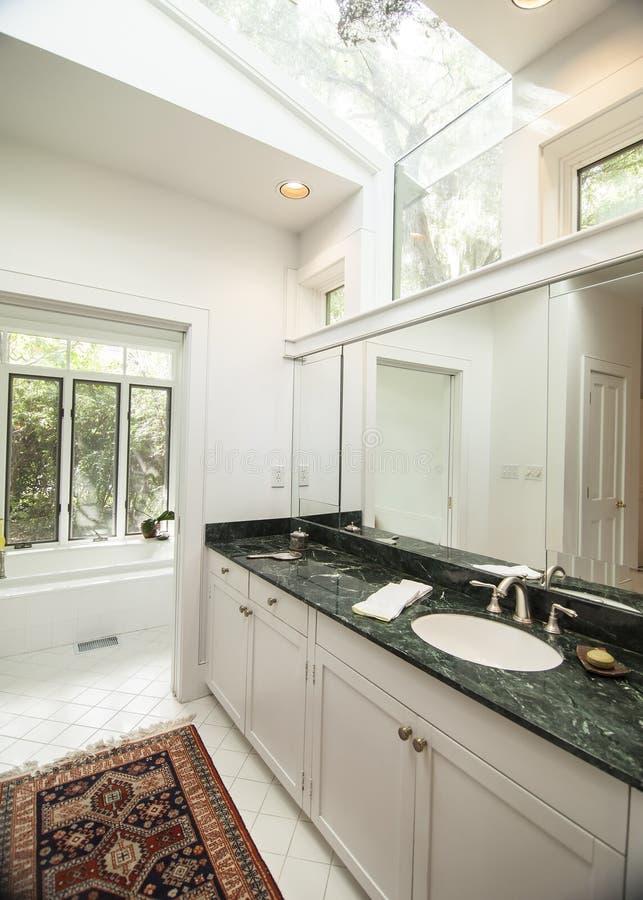 Eenvoudige moderne badkamers met zwarte granietteller stock afbeeldingen