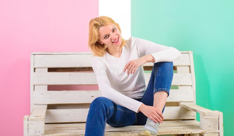 Eenvoudige Schoonheid Zij is eenvoudig schitterend Mooie jonge vrouwenglimlach terwijl het zitten op bank tegen roze achtergrond  royalty-vrije stock foto