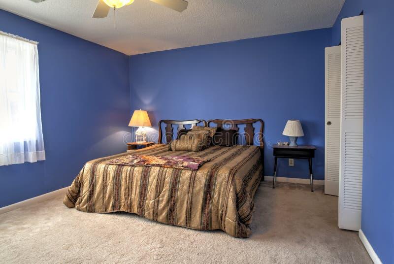 Eenvoudige slaapkamer met blauwe muren stock fotografie