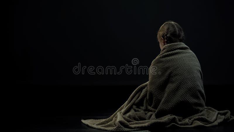 Eenzaam dakloos jong geitje in plaidzitting alleen in donkere plaats, wees backview stock fotografie