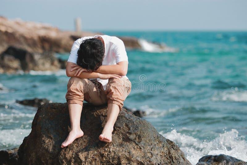 Eenzaam droevig jong Aziatisch die mensengevoel bij de natuurlijke overzeese kust wordt teleurgesteld royalty-vrije stock foto's