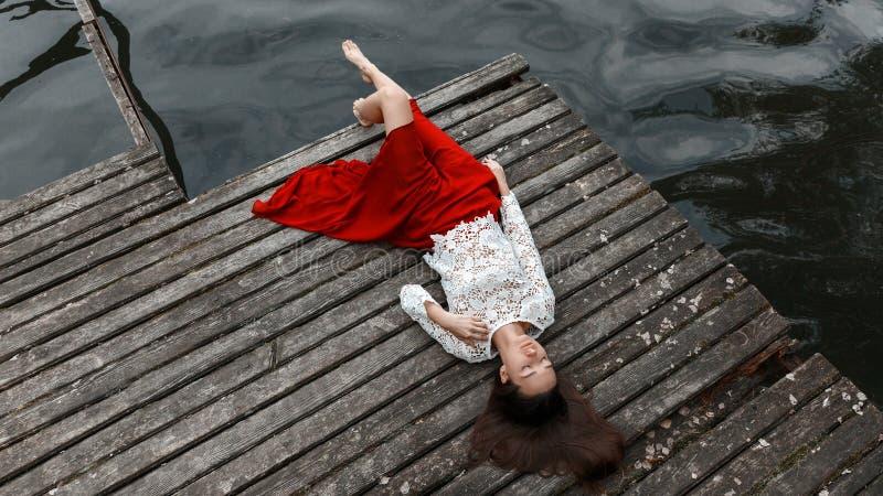 Eenzaam Europees meisje in rode rok op de brug stock afbeelding