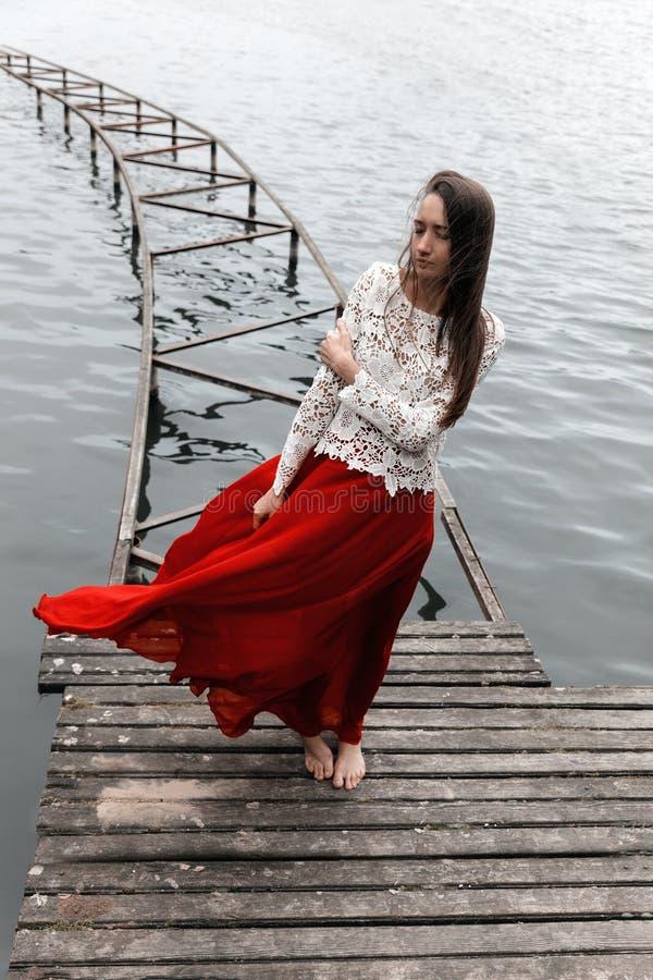 Eenzaam Europees meisje in rode rok op de brug stock afbeeldingen