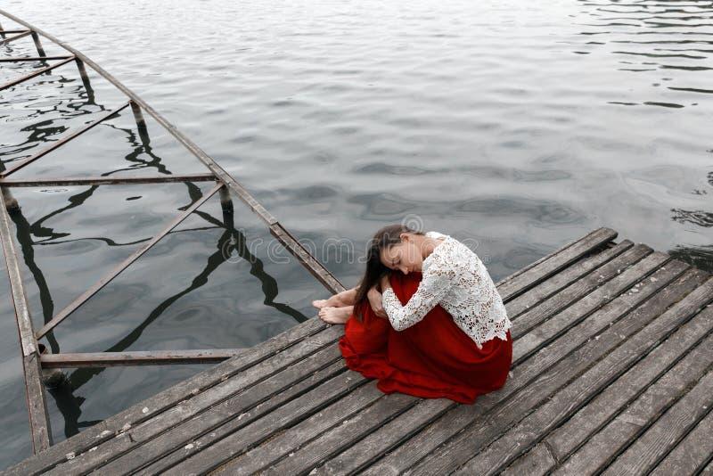 Eenzaam Europees meisje in rode rok op de brug royalty-vrije stock fotografie