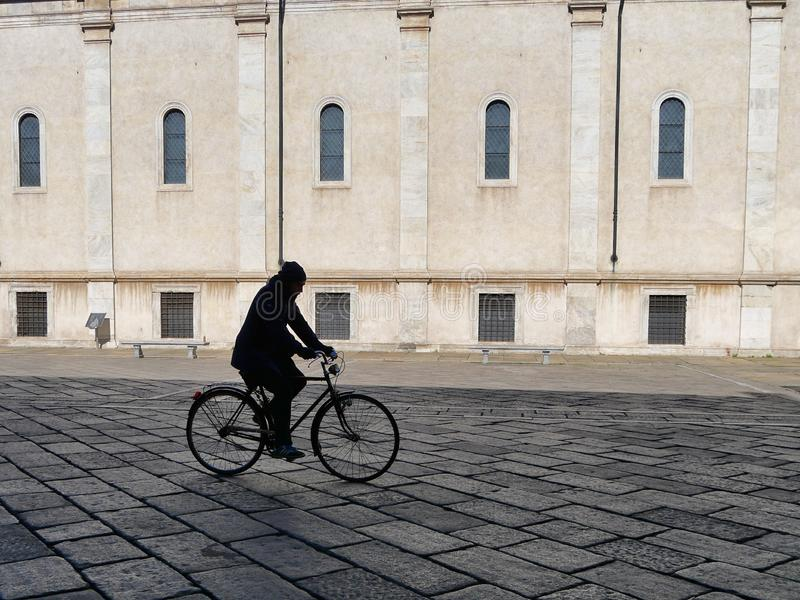 Eenzaam fietsersilhouet in stedelijke gang de stad in stock fotografie