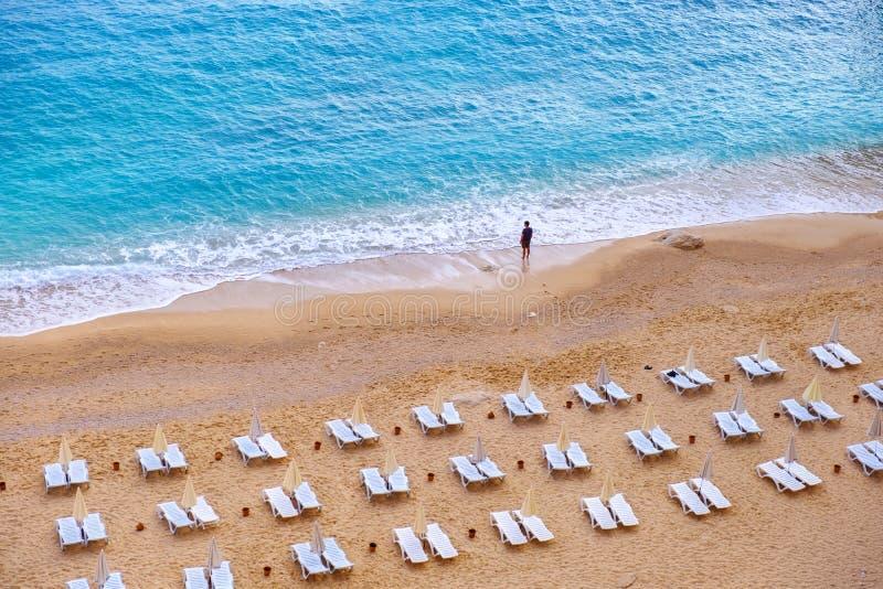 Eenzaam figuur van een mens die zich door de kust op een verlaten Kaputas-strand, Turkije bevinden royalty-vrije stock afbeelding