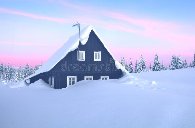 Eenzaam houtplattelandshuisje in de winter stock afbeeldingen