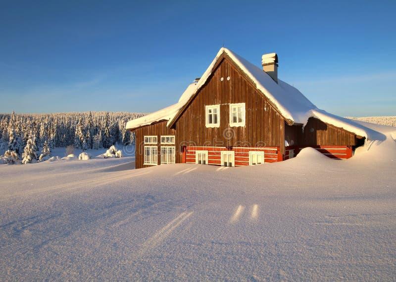 Eenzaam houtplattelandshuisje in de winter stock fotografie