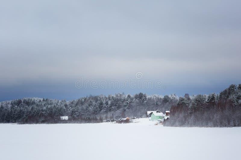 Eenzaam huis houten in het bos op de bank van een bevroren de wintermeer stock afbeelding